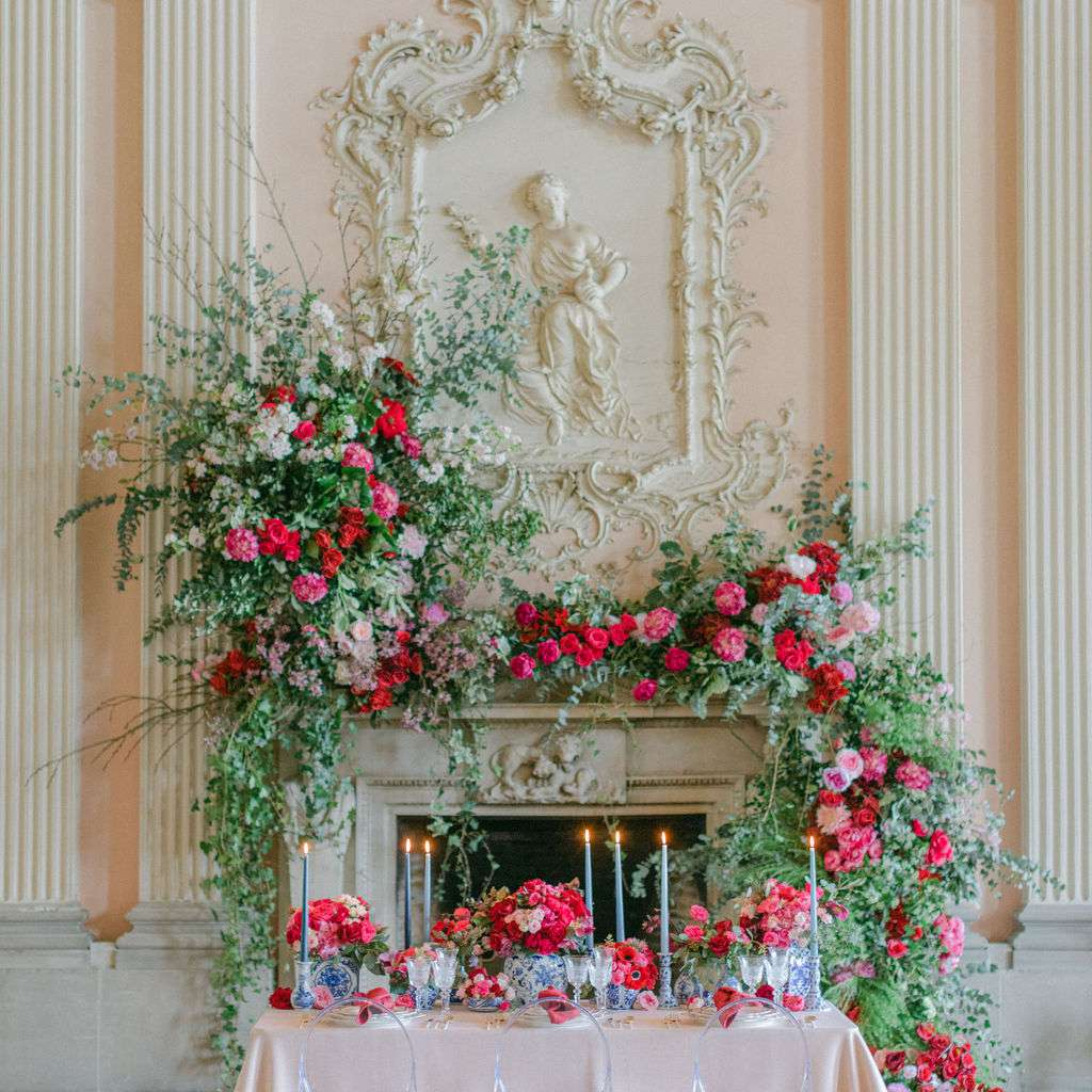 A fireplace and table decorated with pink and red roses and flowers