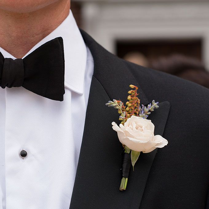A cream rose boutonniere with leafy accents, created by Sara York Grimshaw Designs