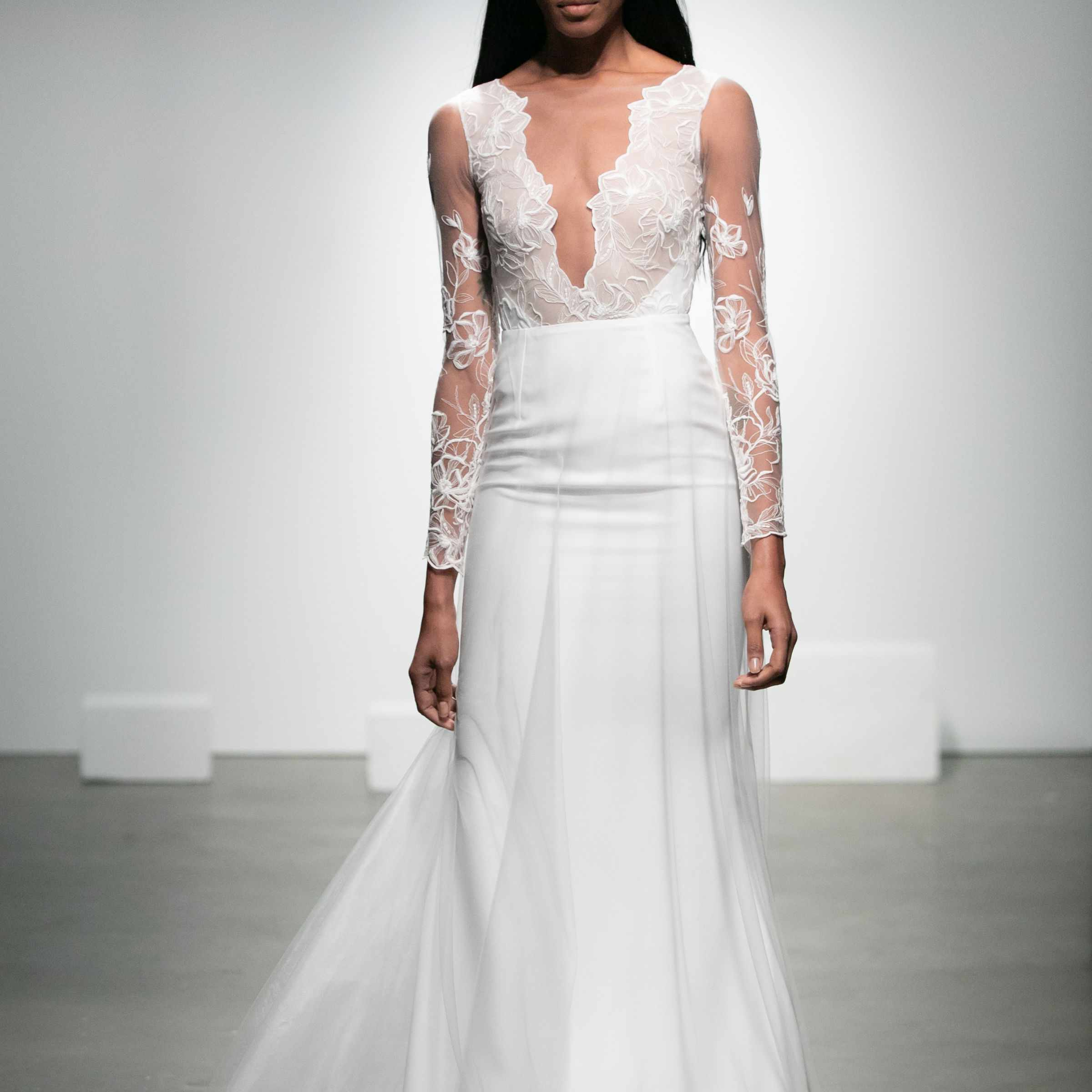 Model in long-sleeve gown with plunging lace top and crepe skirt with tulle overskirt