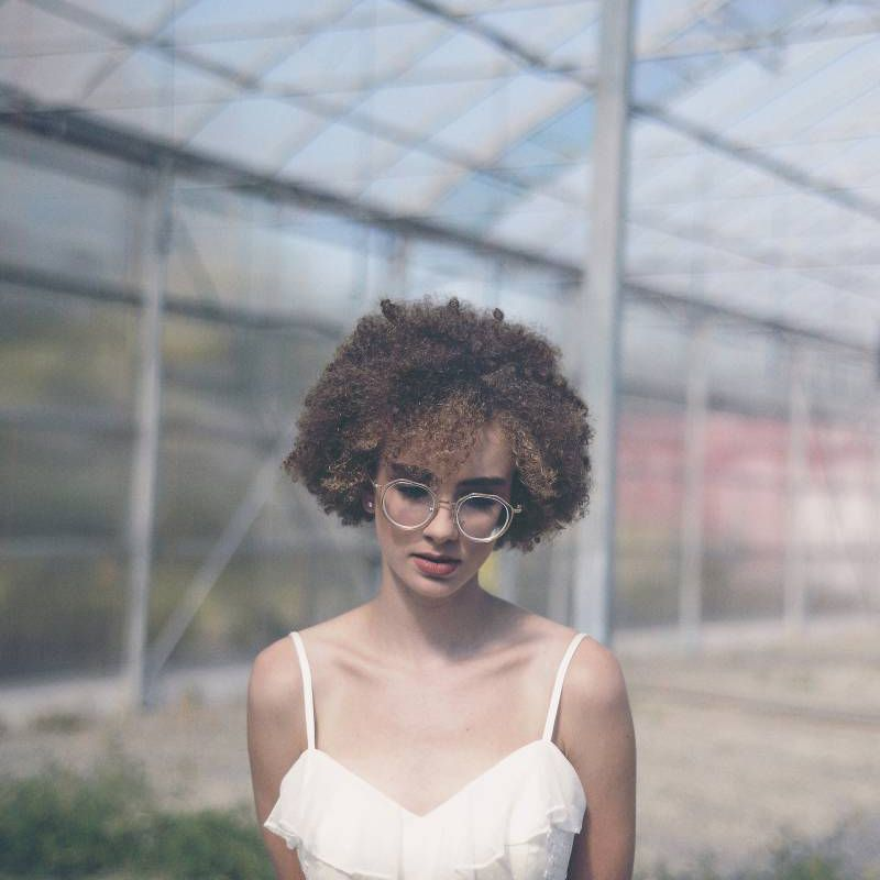 Bride with curly hair wearing round glasses in white wedding dress