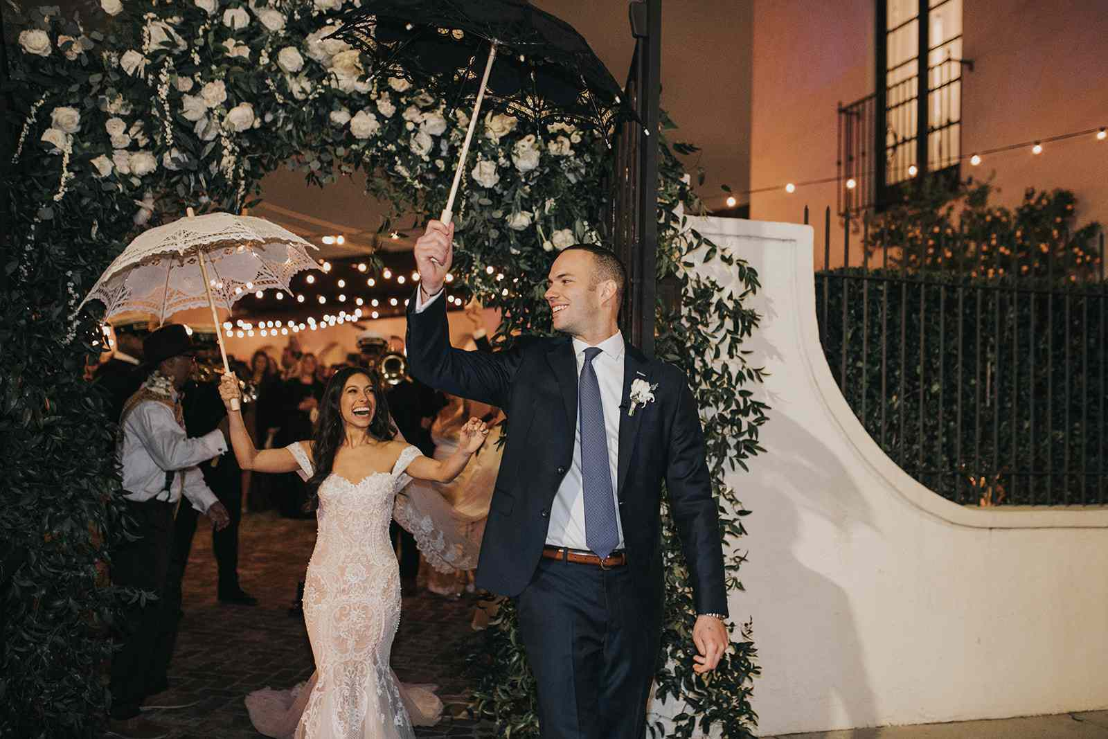 bride and groom holding umbrellas