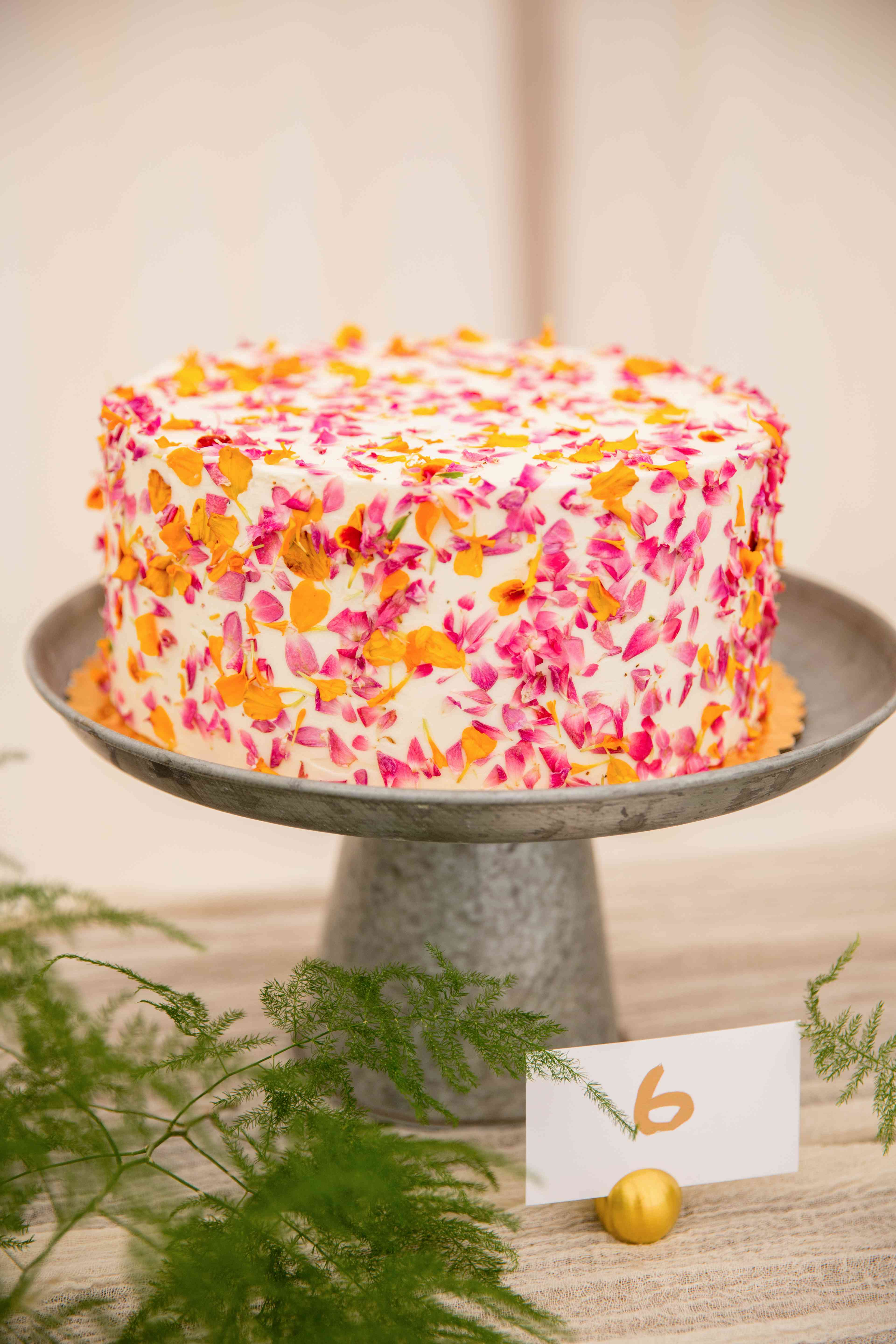 One-tiered white cake decorated with pink and orange edible flowers