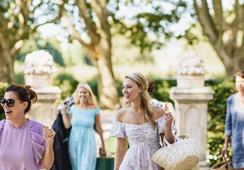 Women in dresses walking into a wedding