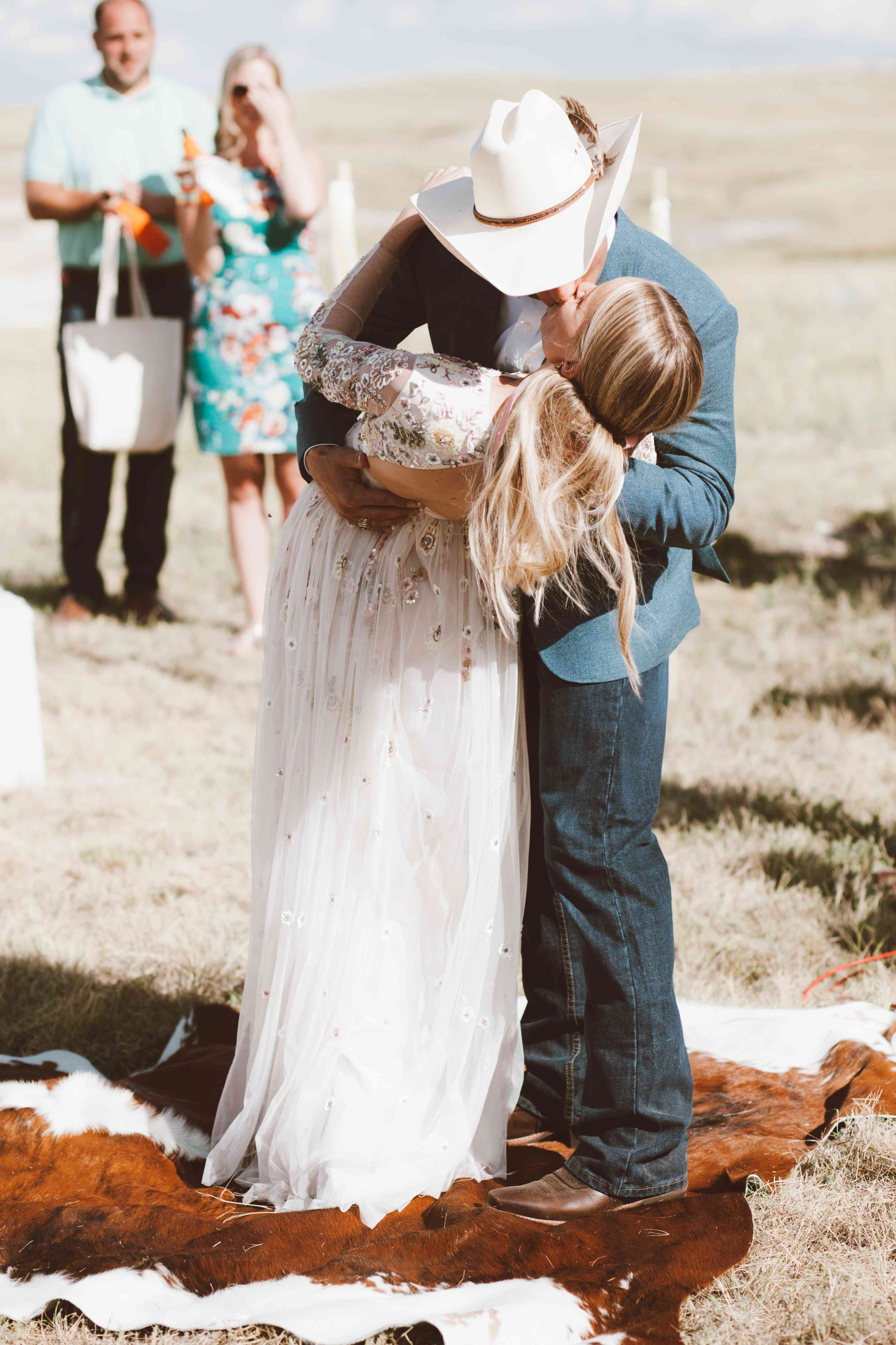 Western groom dipping bride for first kiss