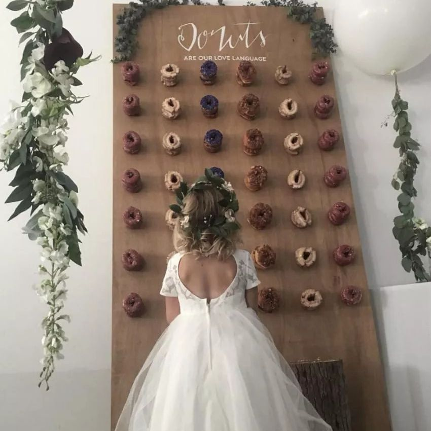 Flower girl standing in front of donut wall