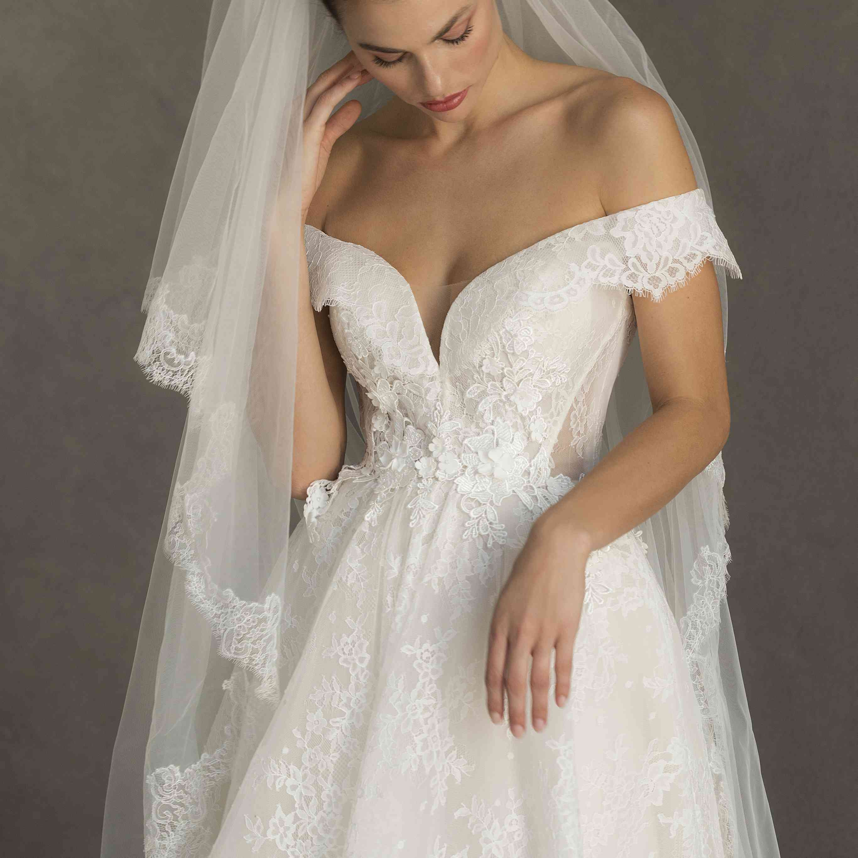 Model in off-the-shoulder lace ballgown with a matching veil
