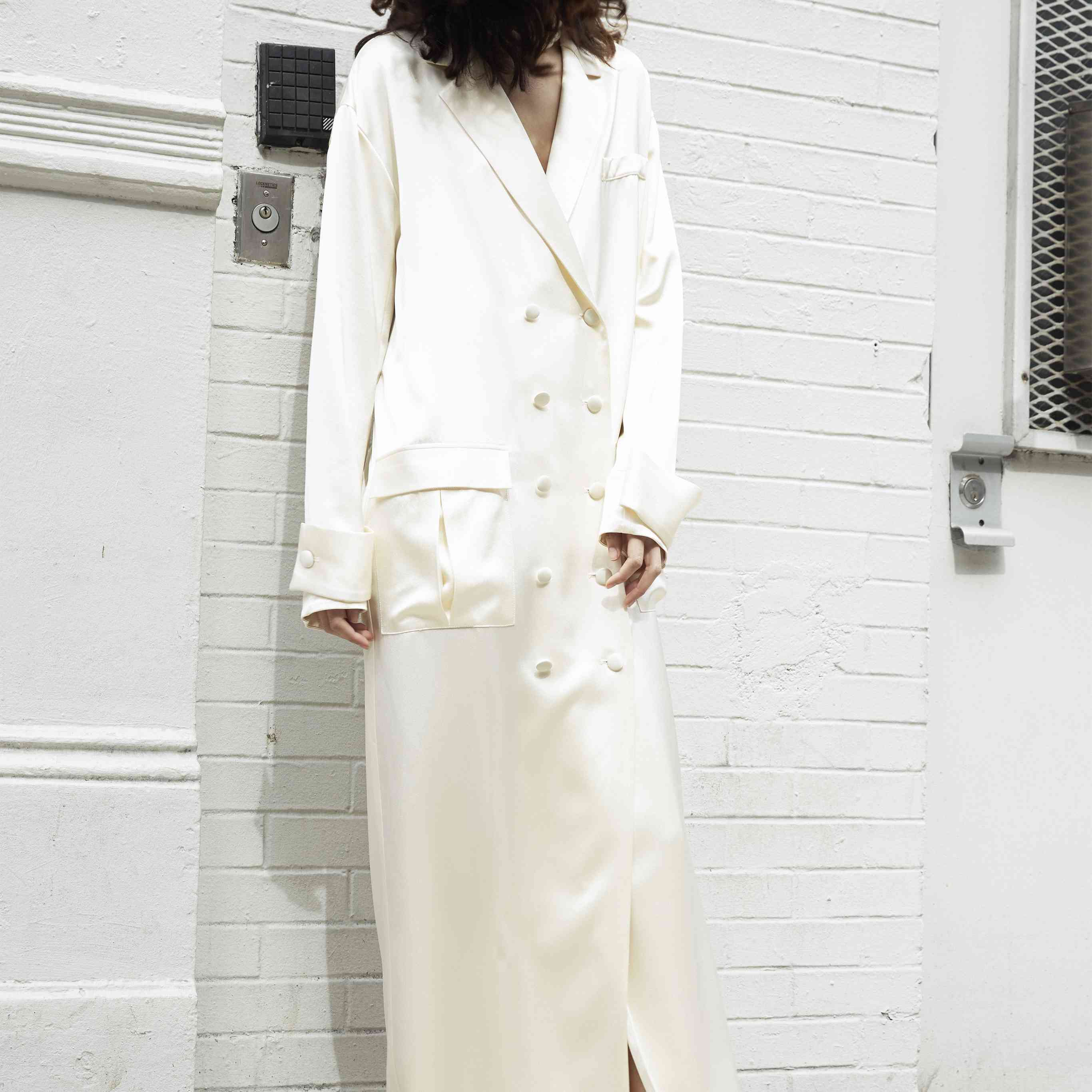 Model in long sleeve wedding blazer dress