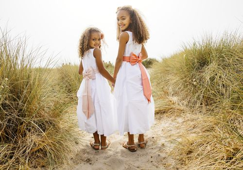 Two young girls as junior bridesmaids at a beach wedding
