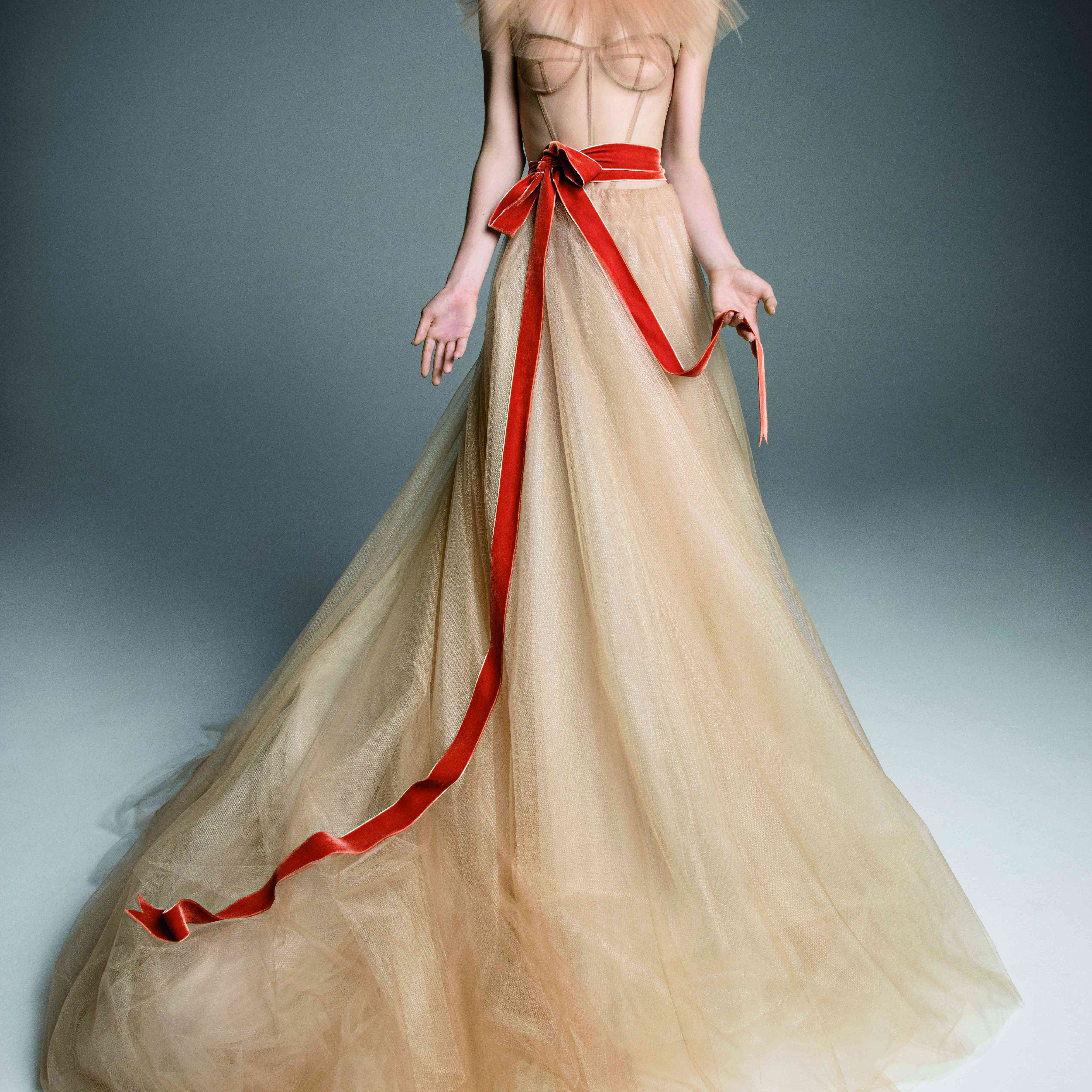 Model in a nude tulle A-line spaghetti strap dress with a corset bodice accented with a red ribbon at the waist