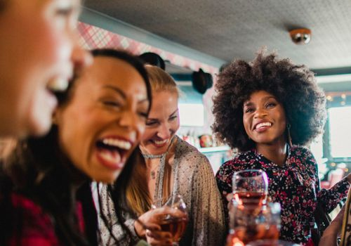 Several women laughing and drinking wine