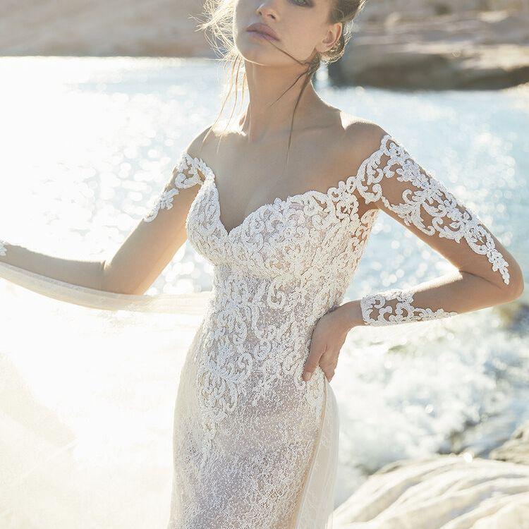 Model in embellished long-sleeve off-the-shoulder wedding gown