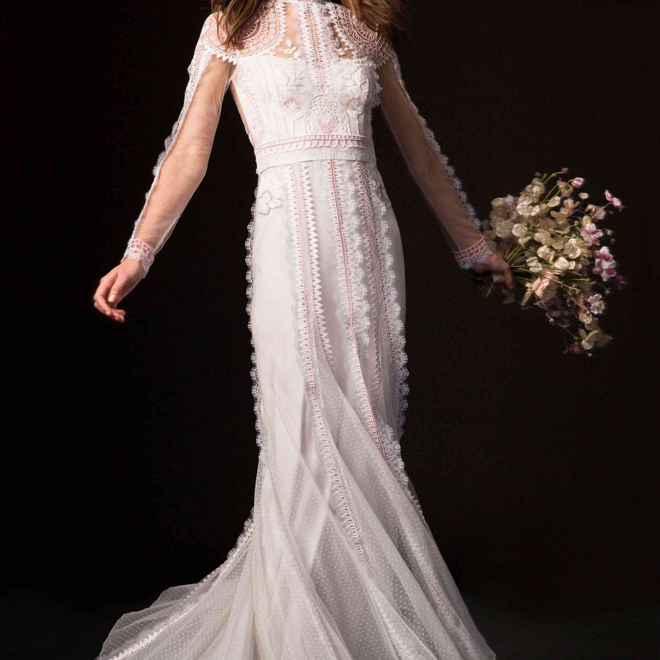 Model in long-sleeve, high-neck gown with pink and white lace embroidery