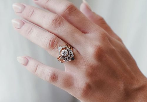 Hand with ring stack of three bands and an engagement ring