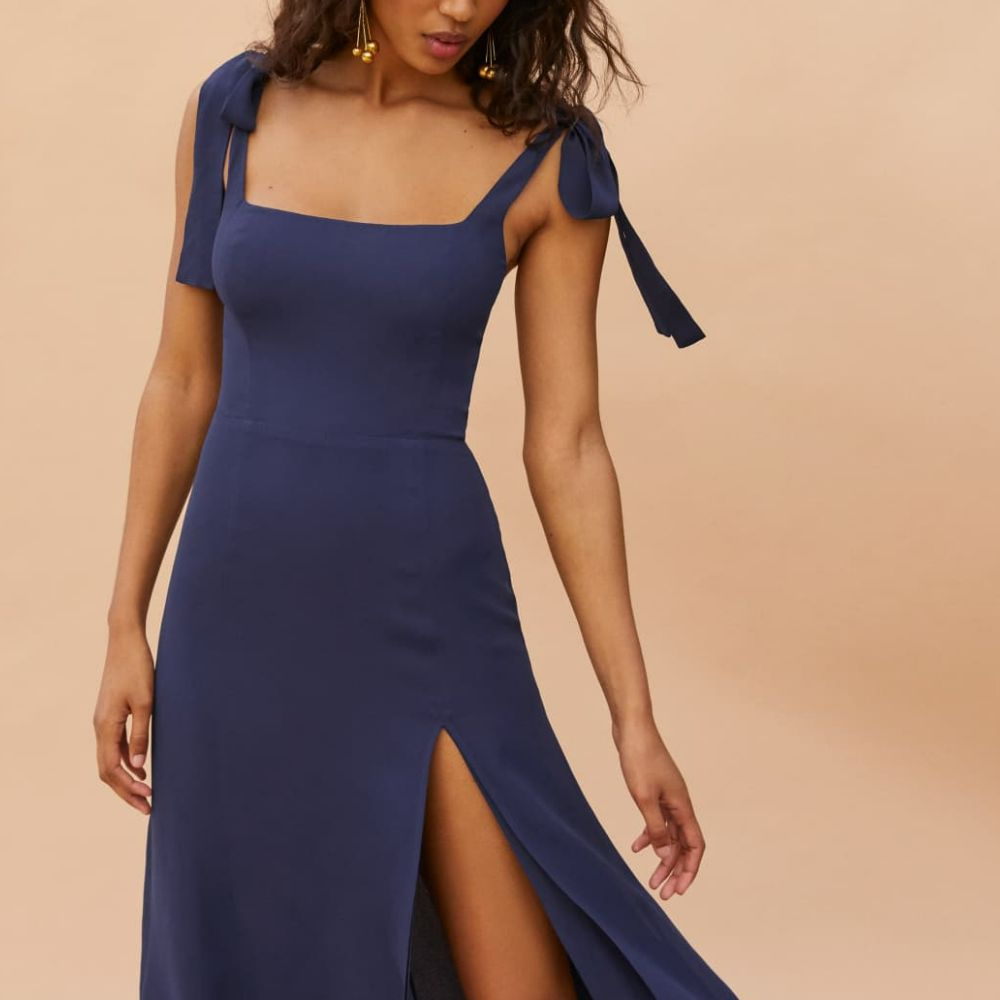 Model in a mid-length blue dress with tie straps and a skirt slit