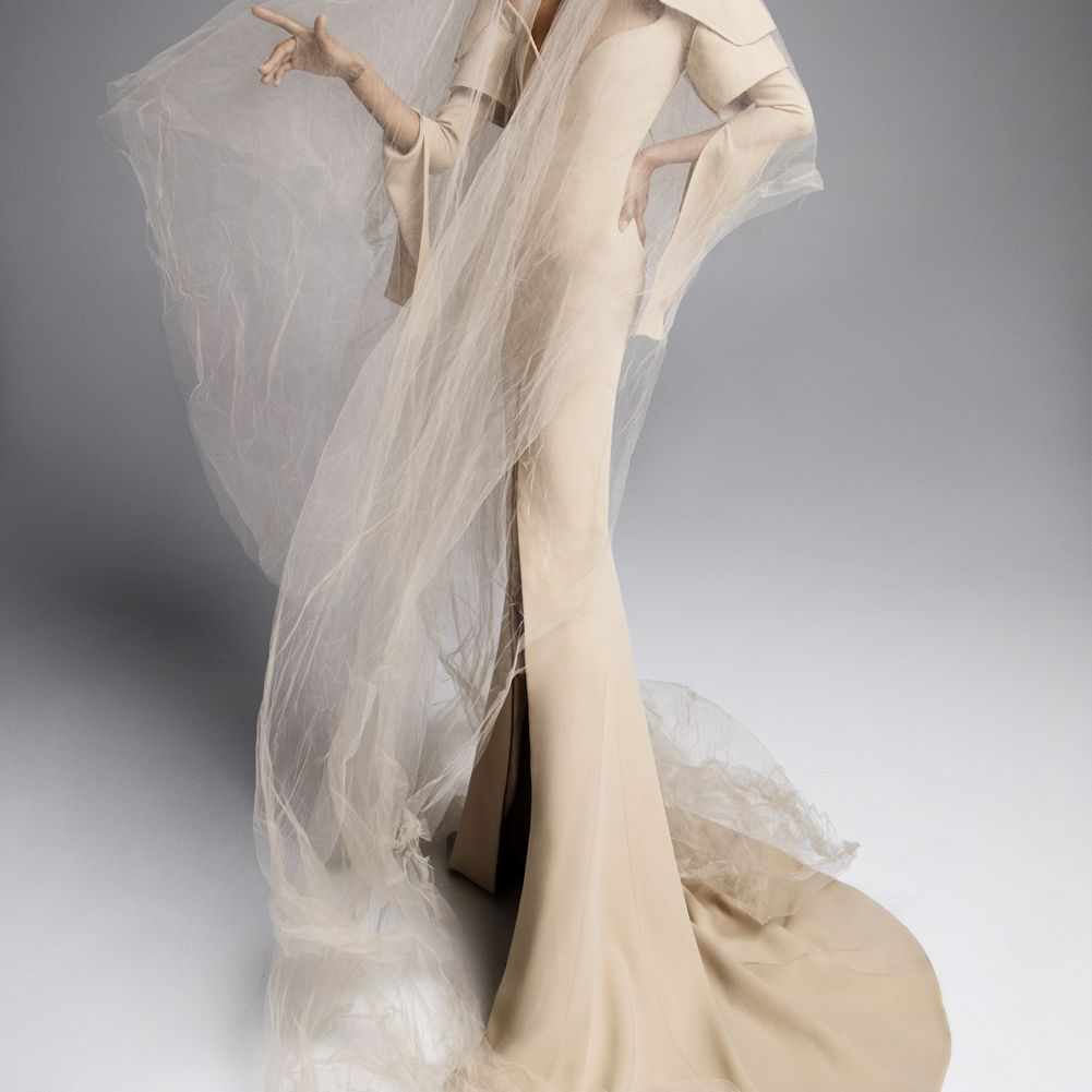 Model in a nude crepe V-neck gown with long sleeves, a high skirt slit, and a nude tulle veil