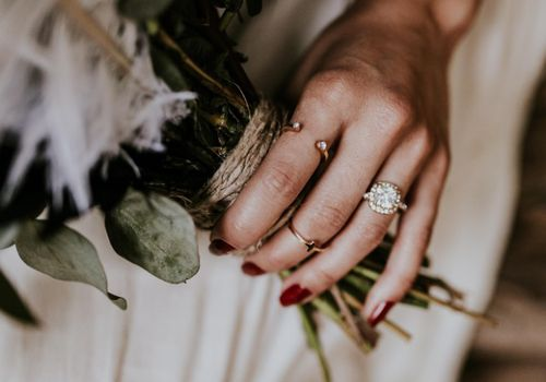 Bride holding bouquet wearing cushion-cut diamond engagement ring