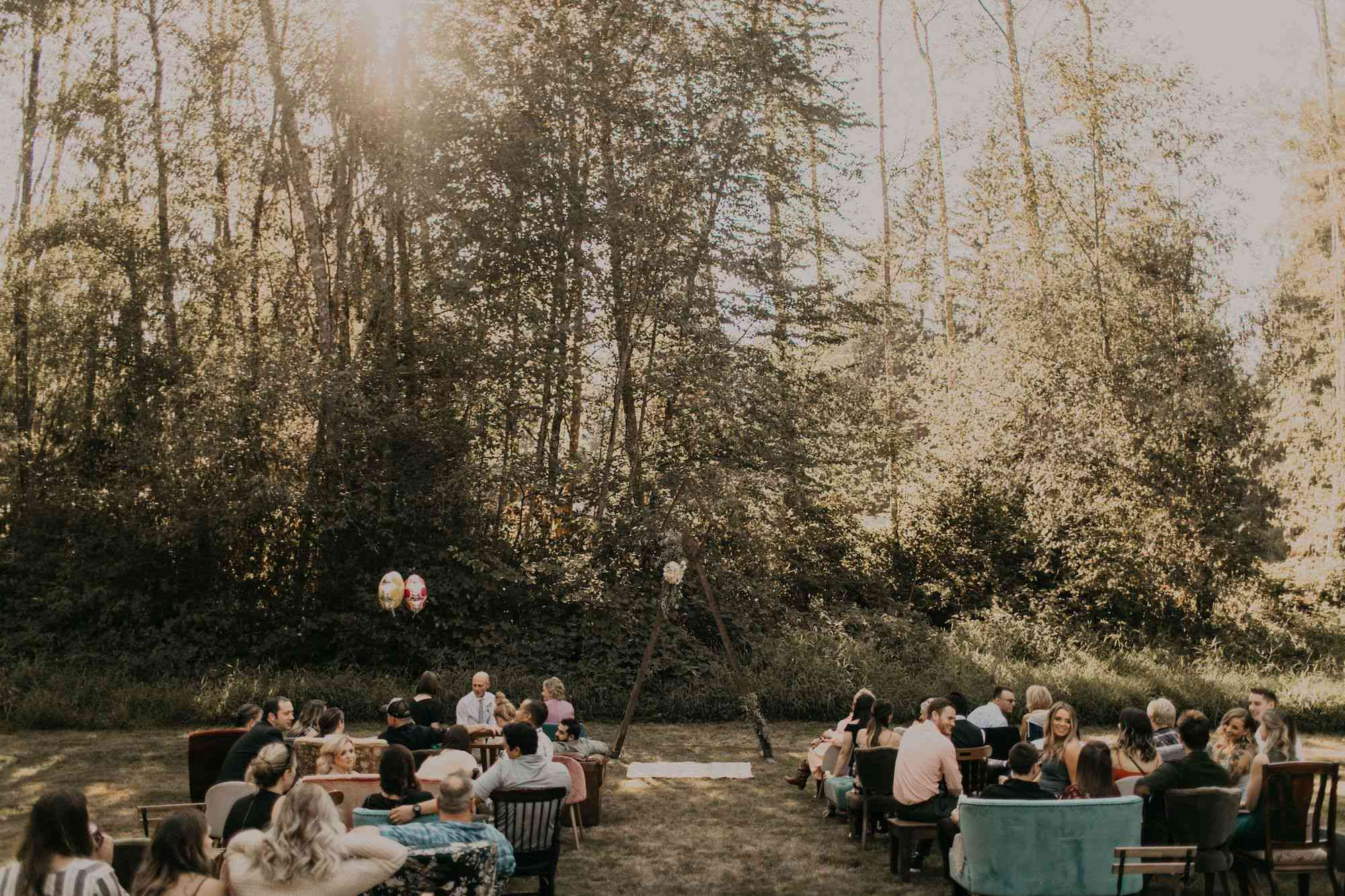 Ceremony aisle in front of trees with a triangle arch and mismatched furnature