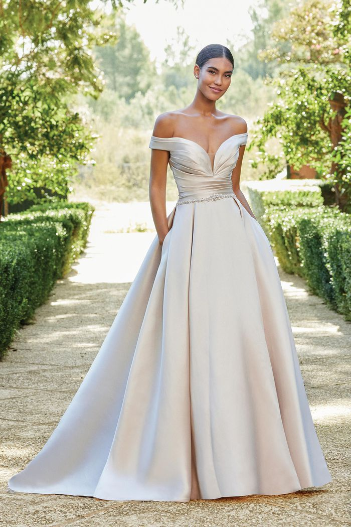 Model in off-the-shoulder ball gown with pockets