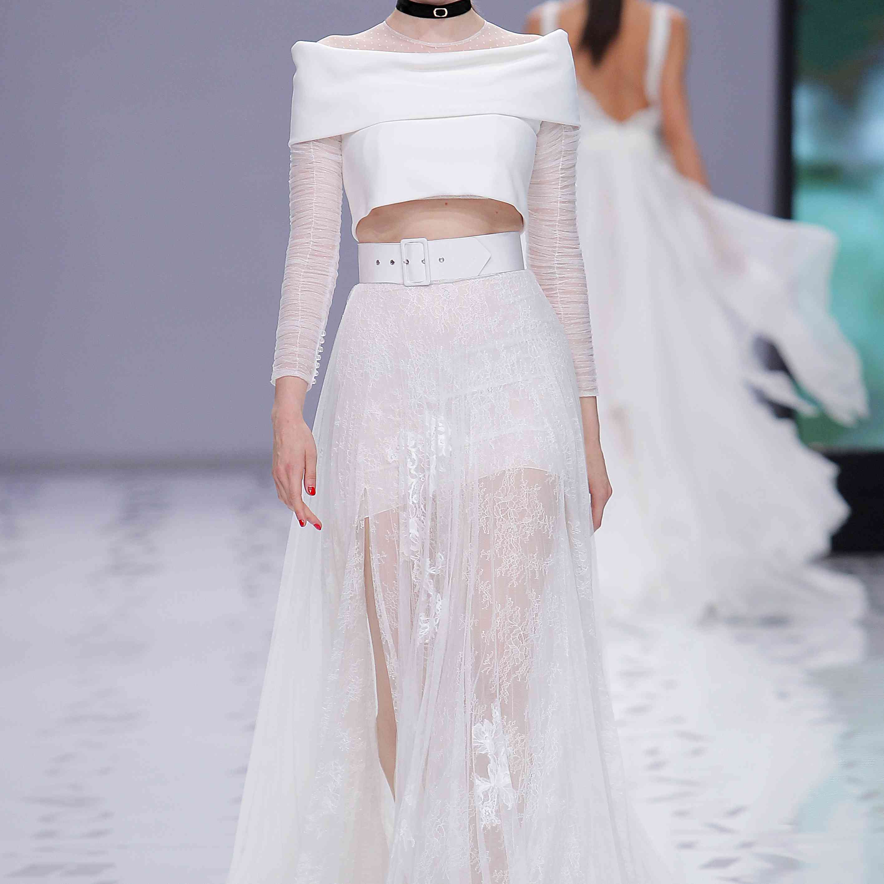 Model in off-the-shoulder crepe crop-top with foldover neckline and gathered tulle long sleeves and an A-line lace and tulle full skirt with front slit, worn with thick white belt