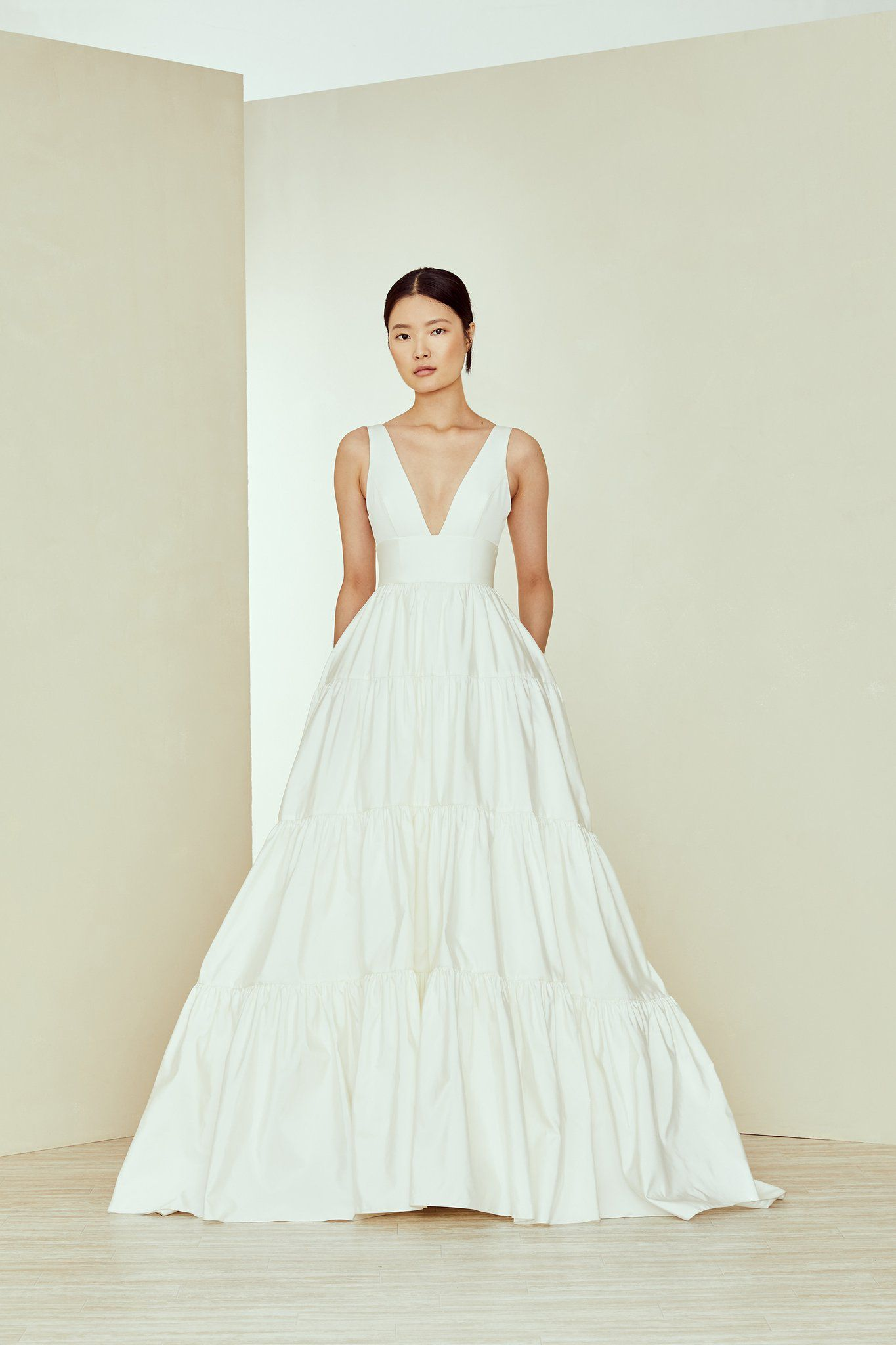 Model in V-neck white wedding gown with tiered skirt and pockets