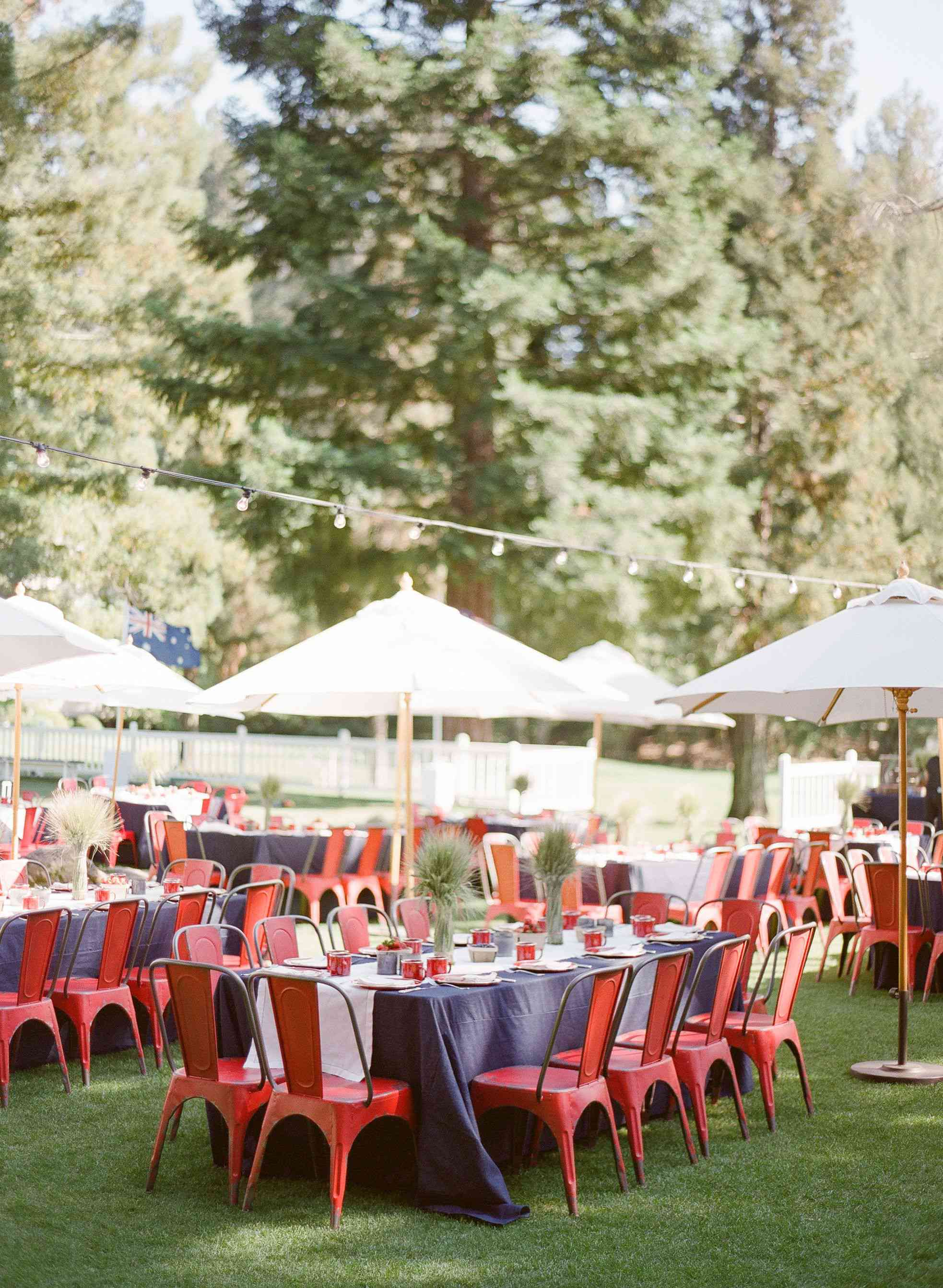 Picnic tables with umbrellas at an outdoor reception