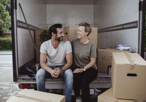 TitleSmiling male and female partners looking at each other while sitting by cardboard boxes in van