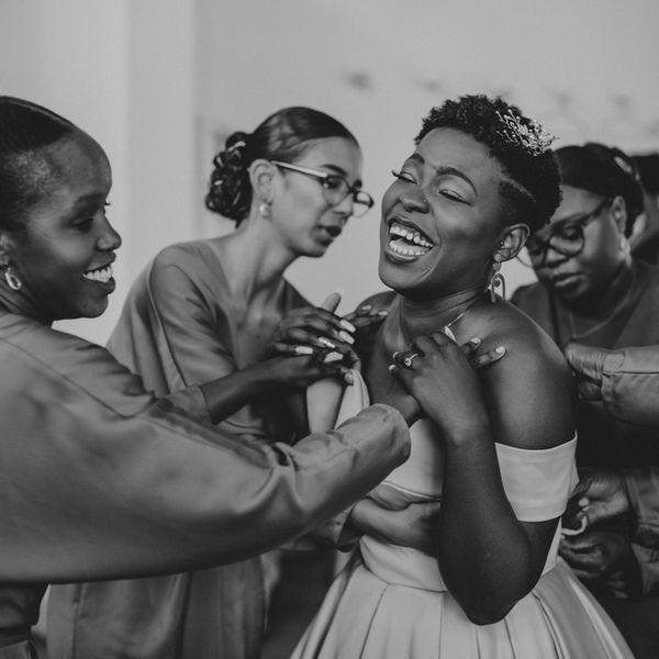 Bridesmaids helping smiling bride put on her dress