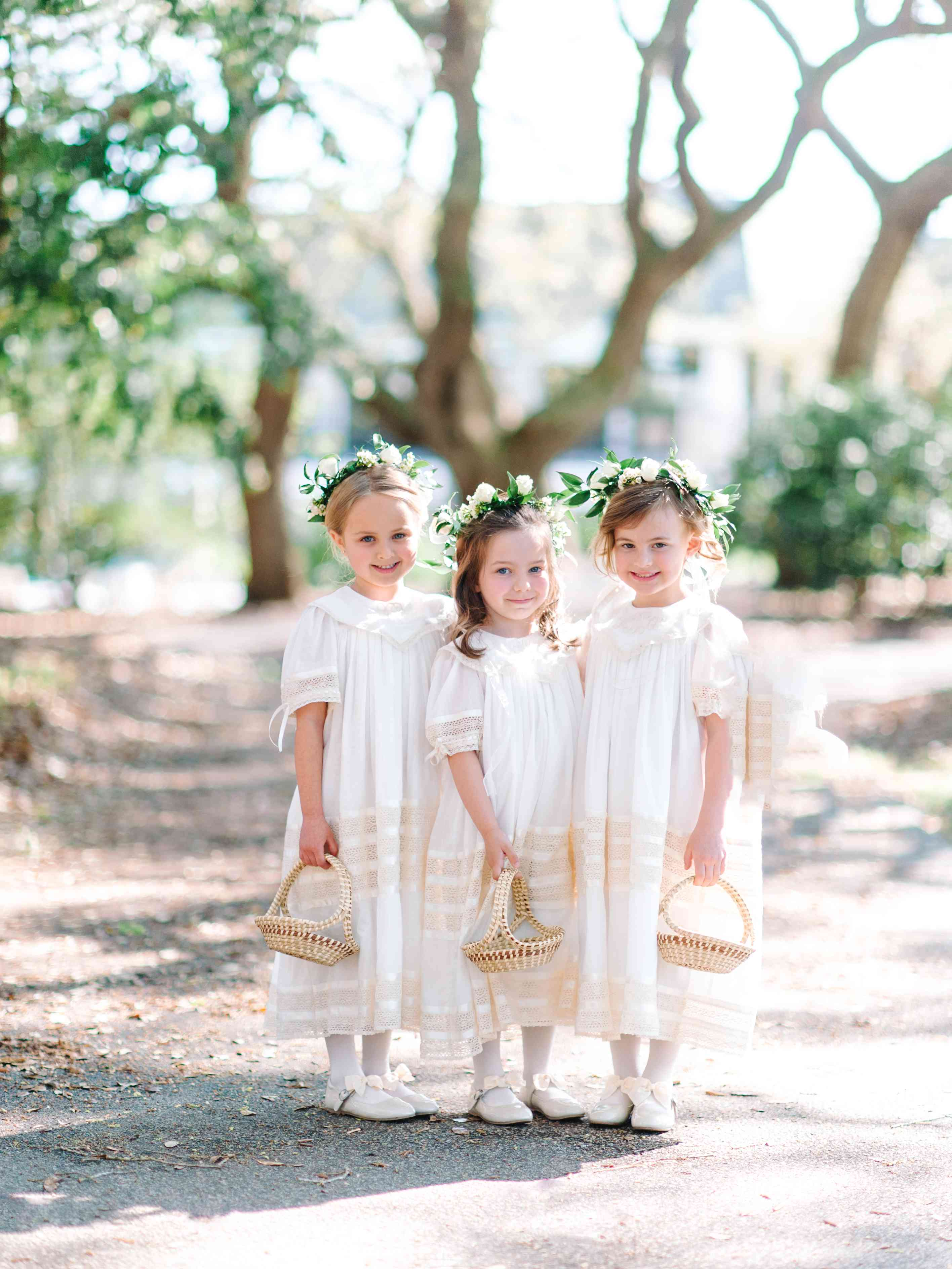 Three flower girls in white dresses and flower crowns holding wicker baskets