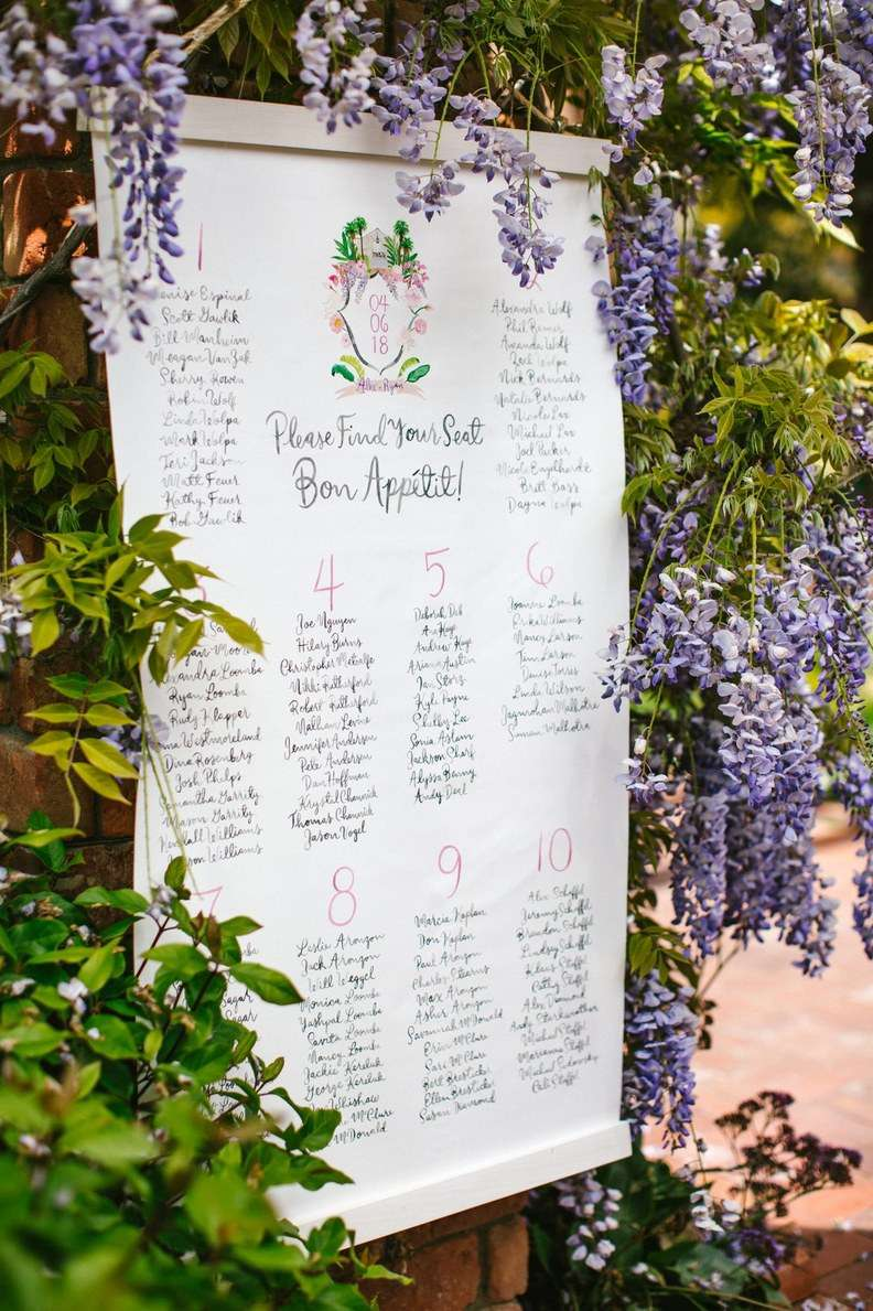 Seating chart with a custom crest surrounded by purple flowers