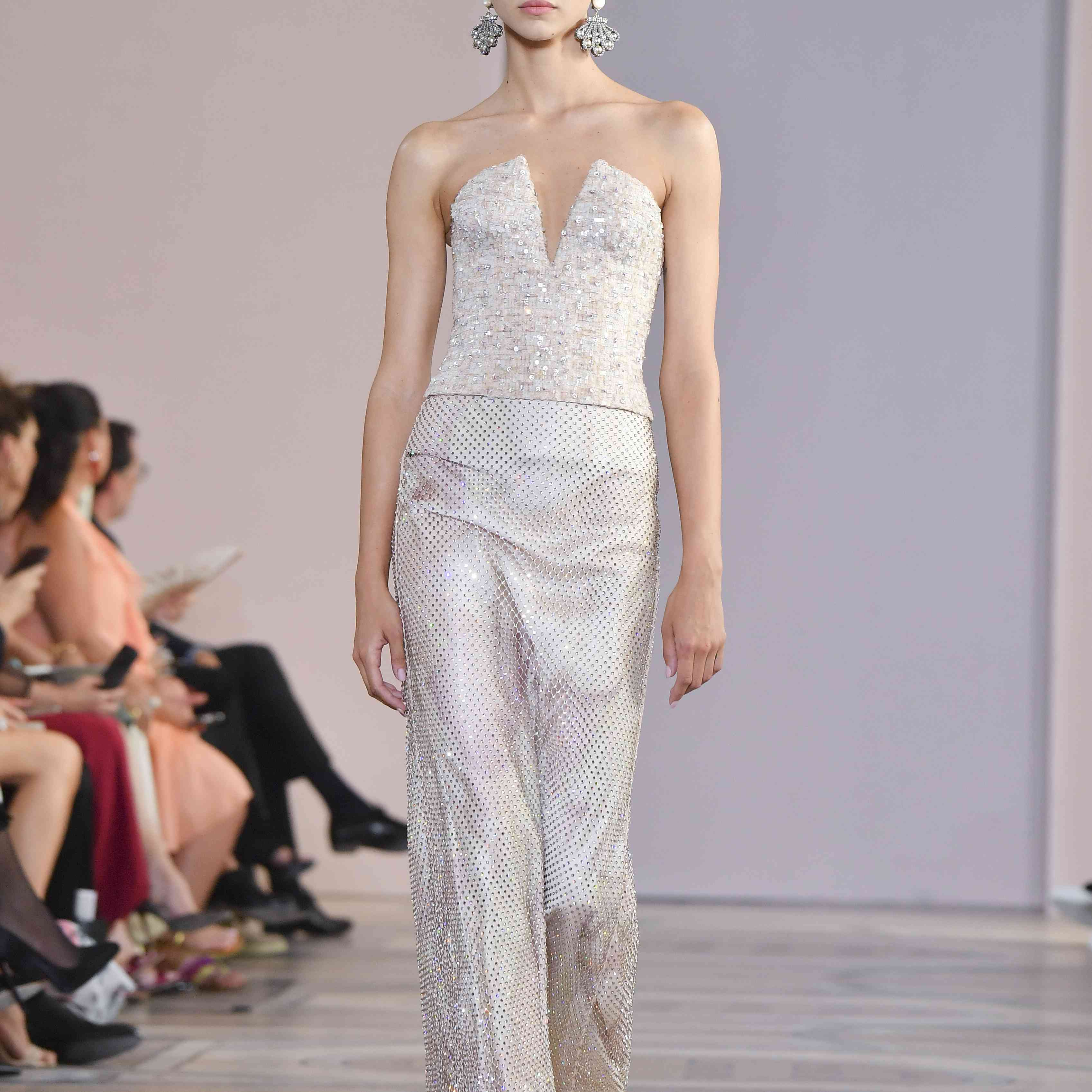 A model walks the runway in deep-cut embellished gown