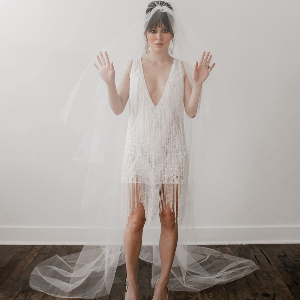 Model wearing Varca Bridal short white wedding dress with fringe and floor length veil