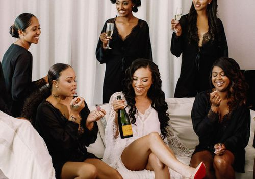 Bride and bridesmaids drinking champagne while getting ready on the morning of the wedding