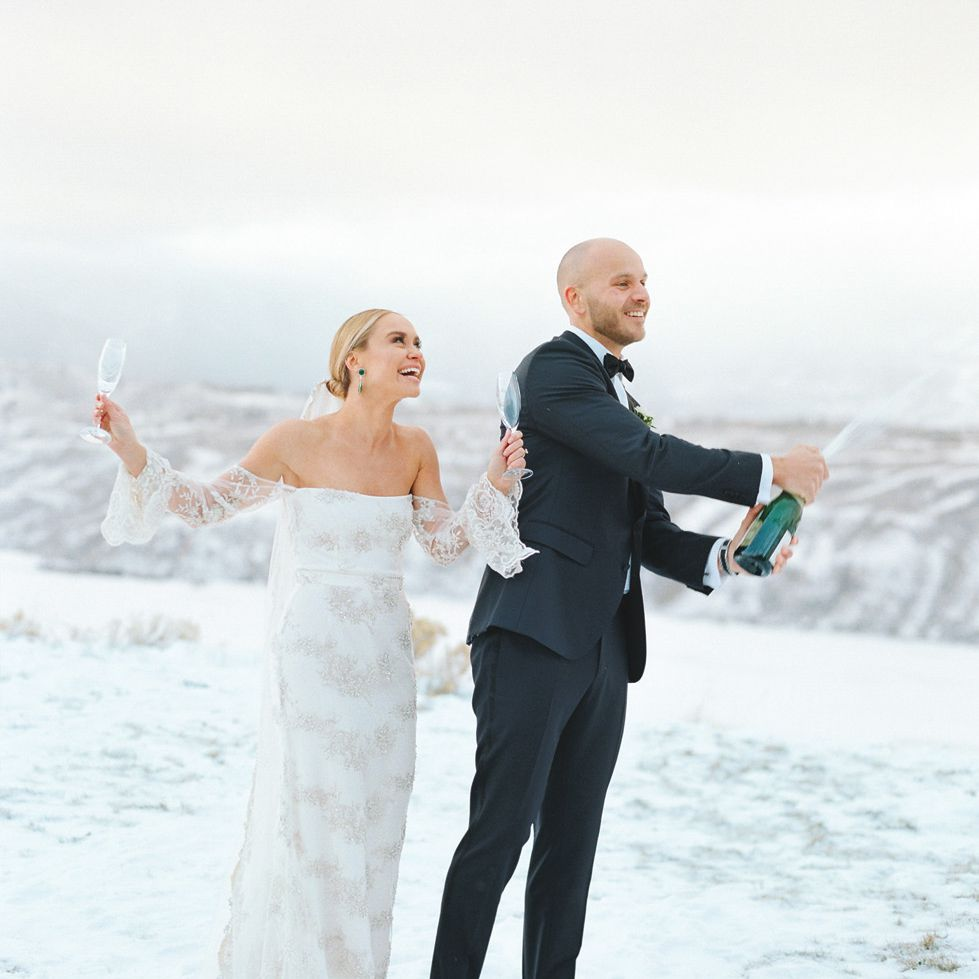Bride and groom popping champagne in the snow outside