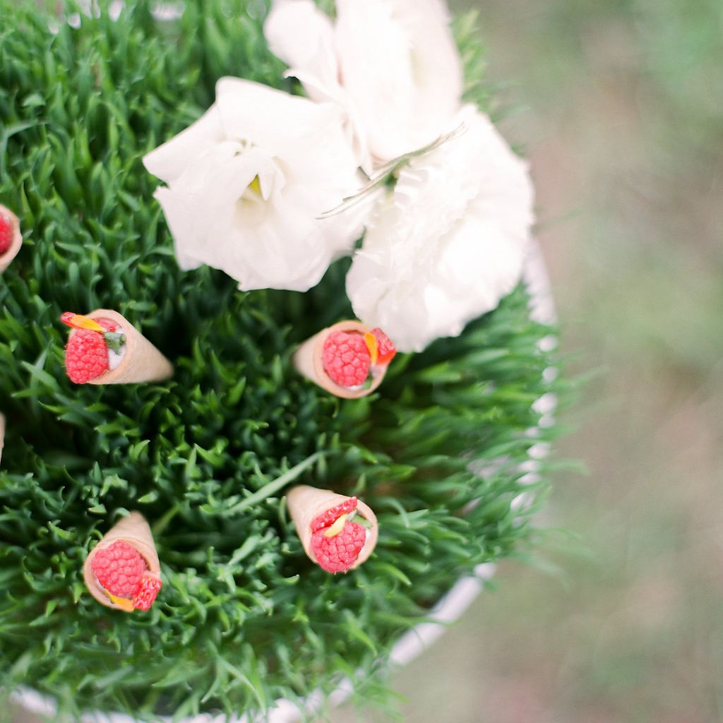 Decorative grass with white roses and fresh raspberries