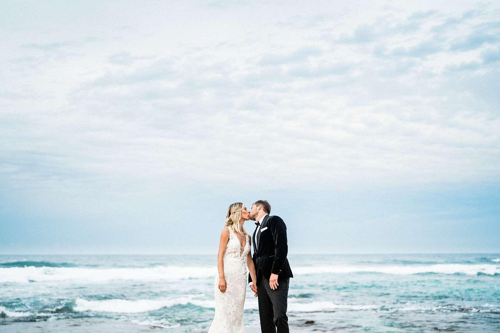 bride and groom in front of ocean