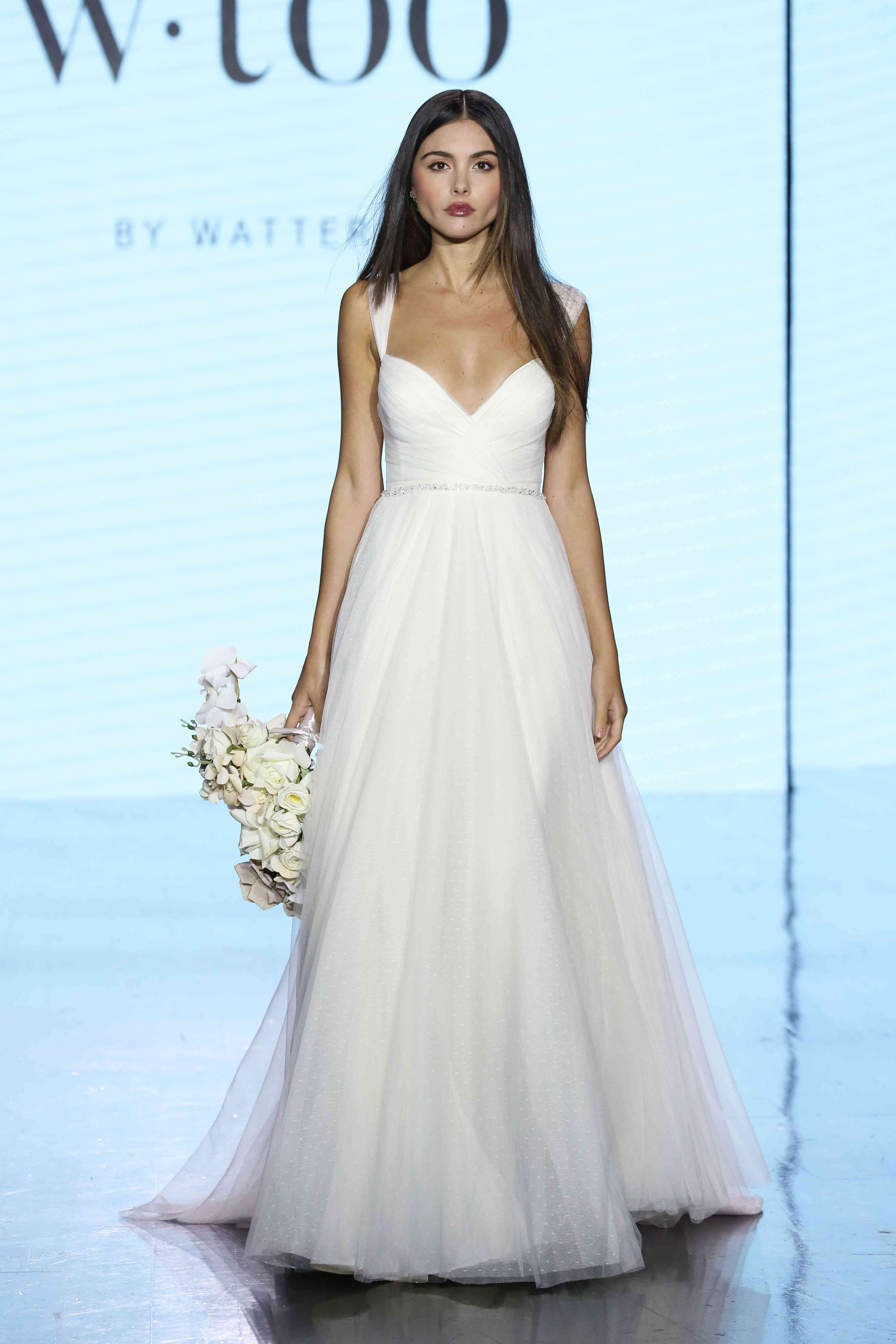 Model in tulle cap-sleeve V-neck A-line gown with a jeweled belt