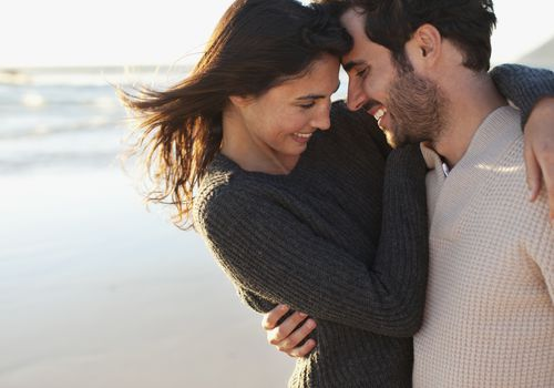 Man and women smiling and hugging on the beach