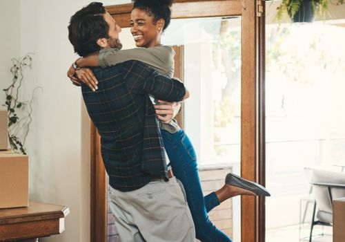 An affectionate middle aged man lifting his wife in celebration in their new home