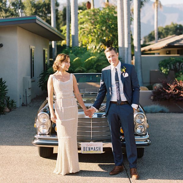 Bride and groom standing in front of car