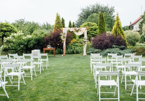 White wedding chairs decorated with fresh flowers on a green grass. Empty wooden chairs for guests on green lawn in the garden prepared for wedding ceremony.