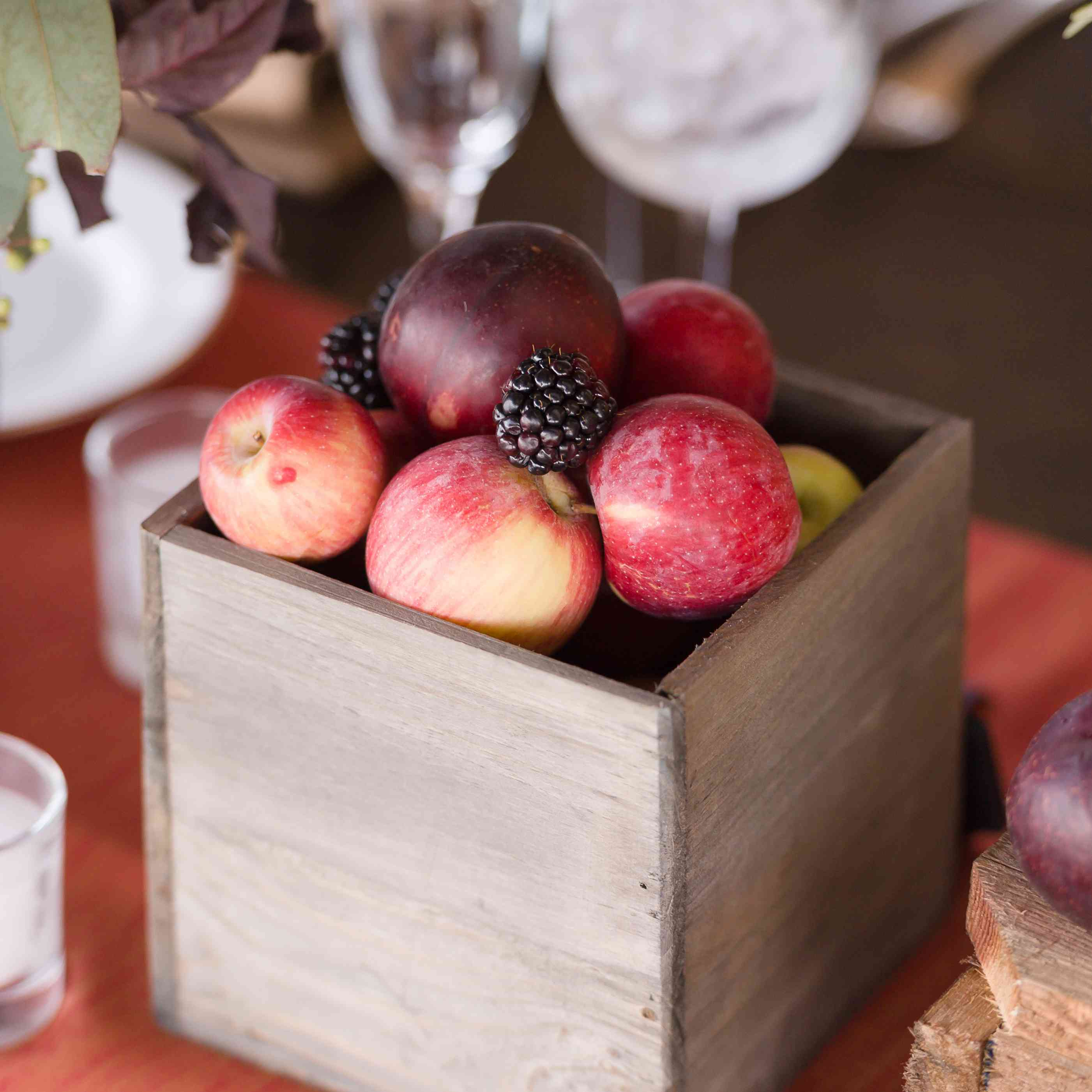 Apples and blackberries in a wooden centerpiece