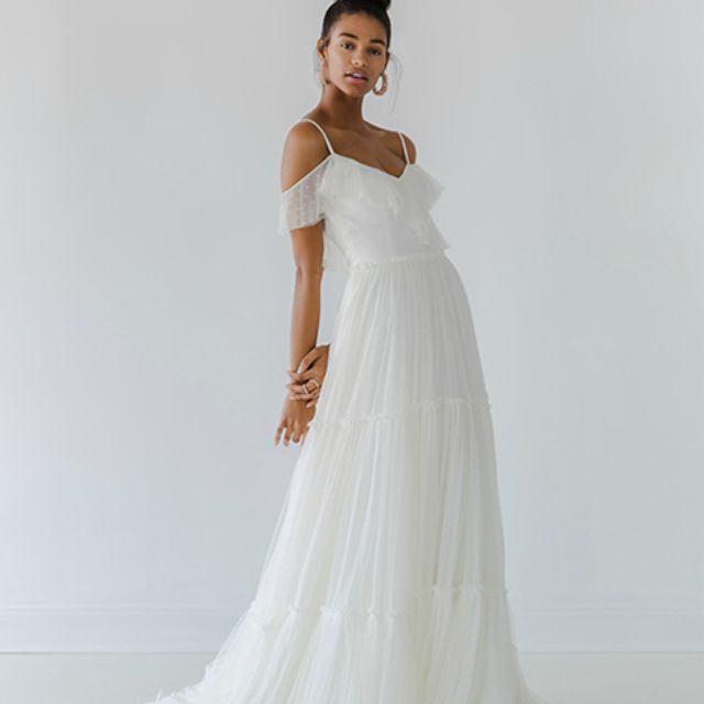 Model in tulle draped shoulder dress with tiered skirt