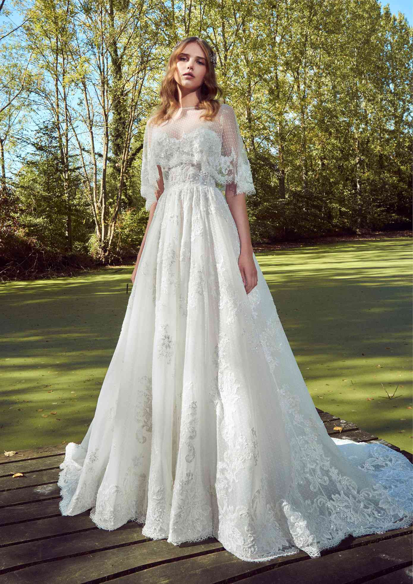 Model in a strapless sweetheart dotted tulle princess gown with beaded lace embroidery and a dotted tulle lace-embroidered capelet with eyelash lace trim
