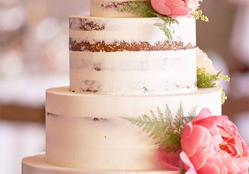 Three tiered white wedding cake with pink flowers