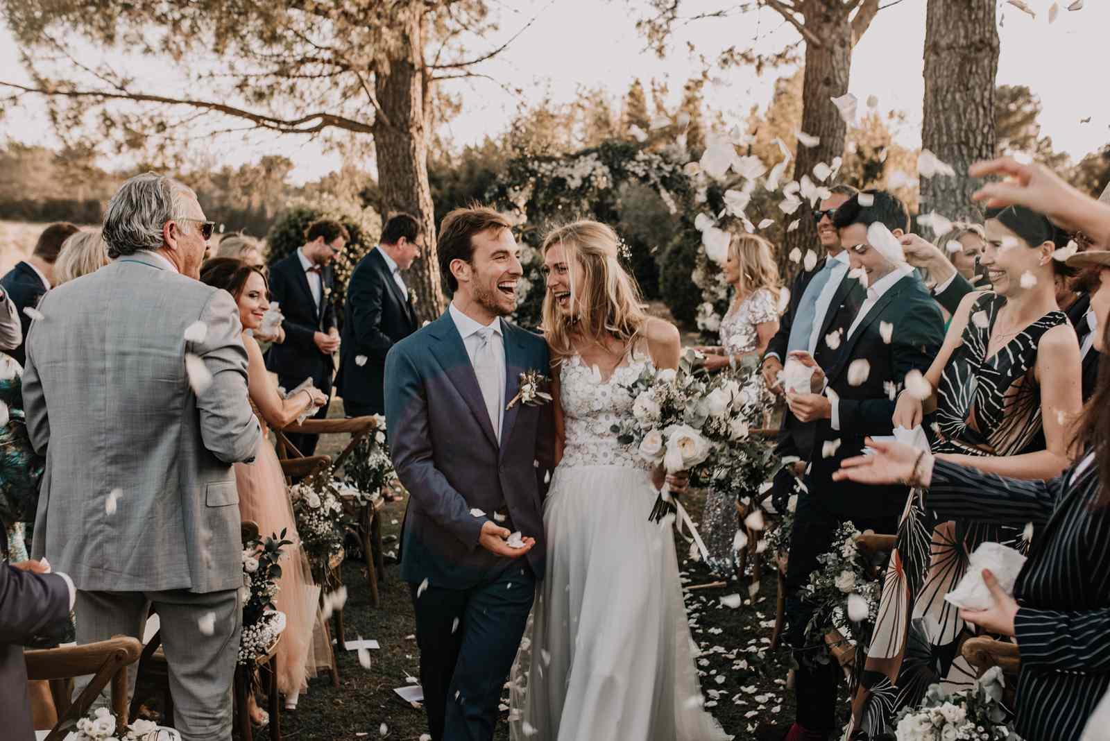 Bride and groom walk back up aisle as people throw flower petals