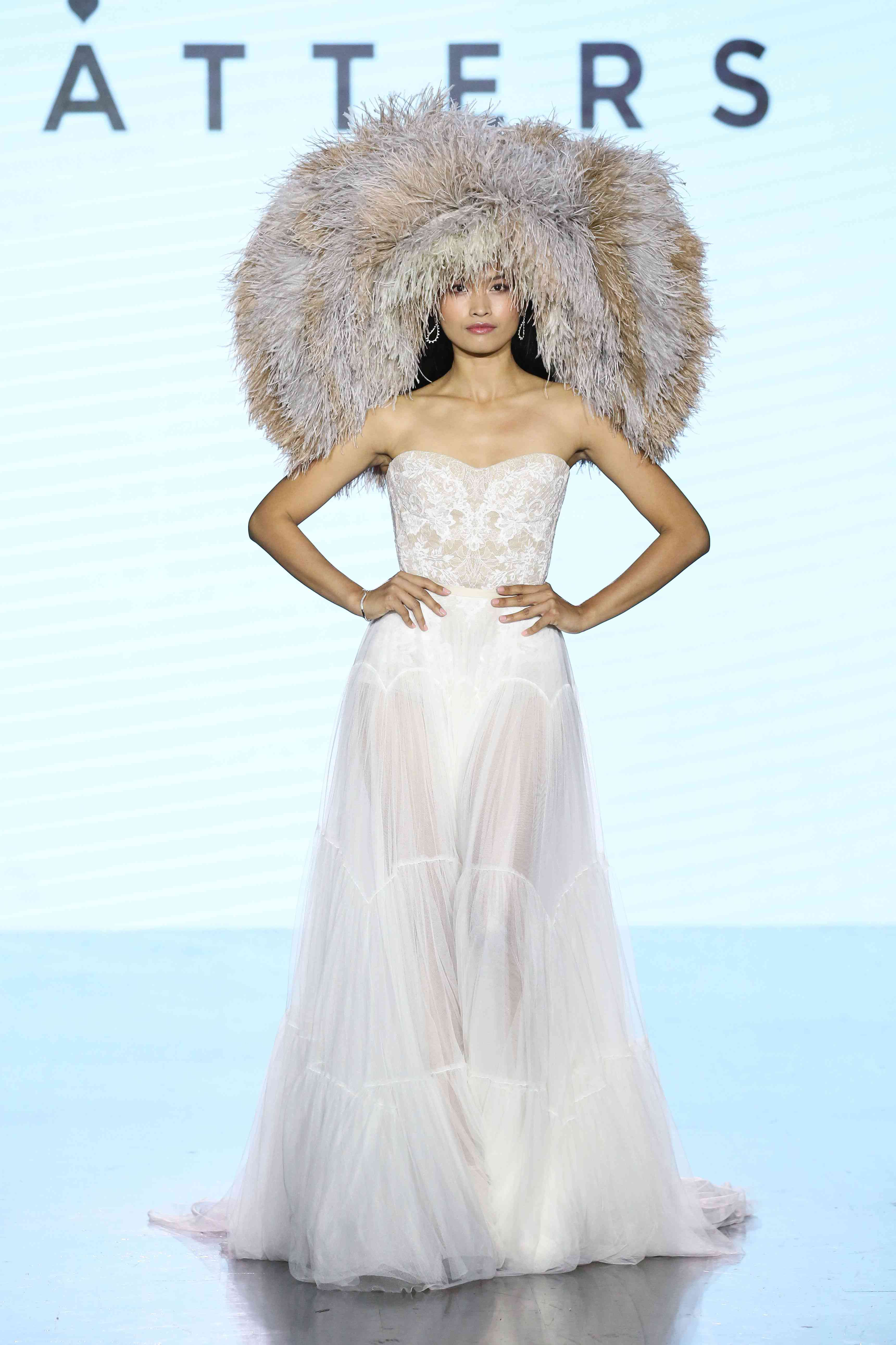 Model on runway in strapless tulle gown with lace bodice