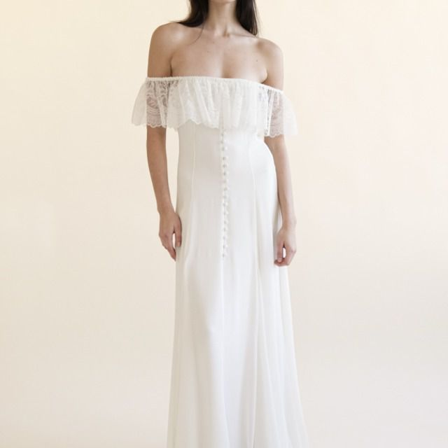 Model in off-the-shoulder gown with ruffles and buttons