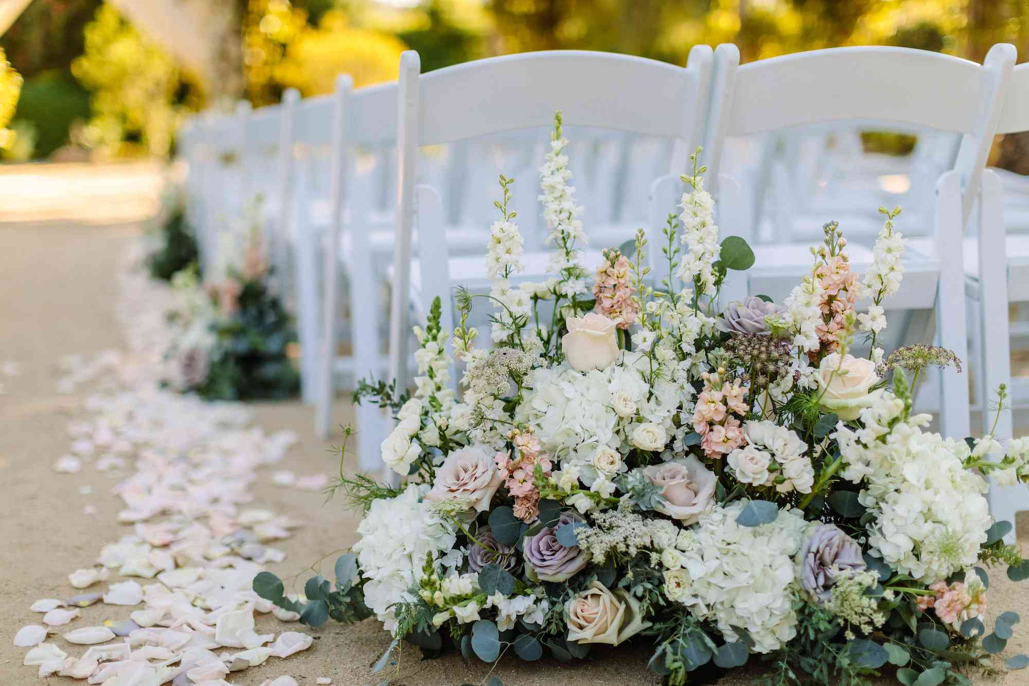 Mixed floral arrangement on the ground at the start of wedding aisle with petals lining aisle