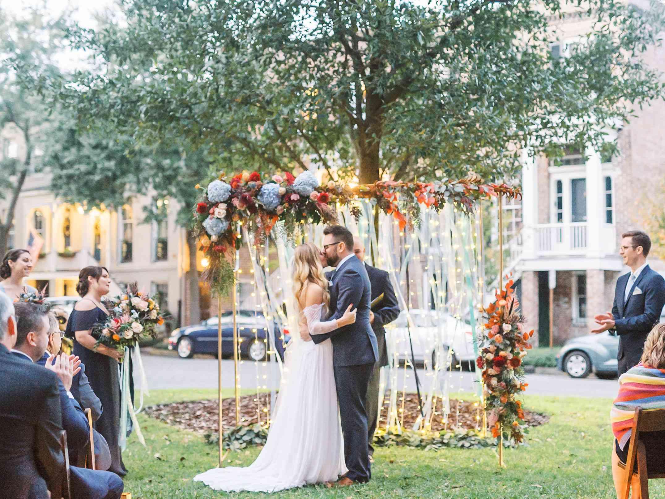 whimsical savannah wedding, bride and groom kissing ceremony