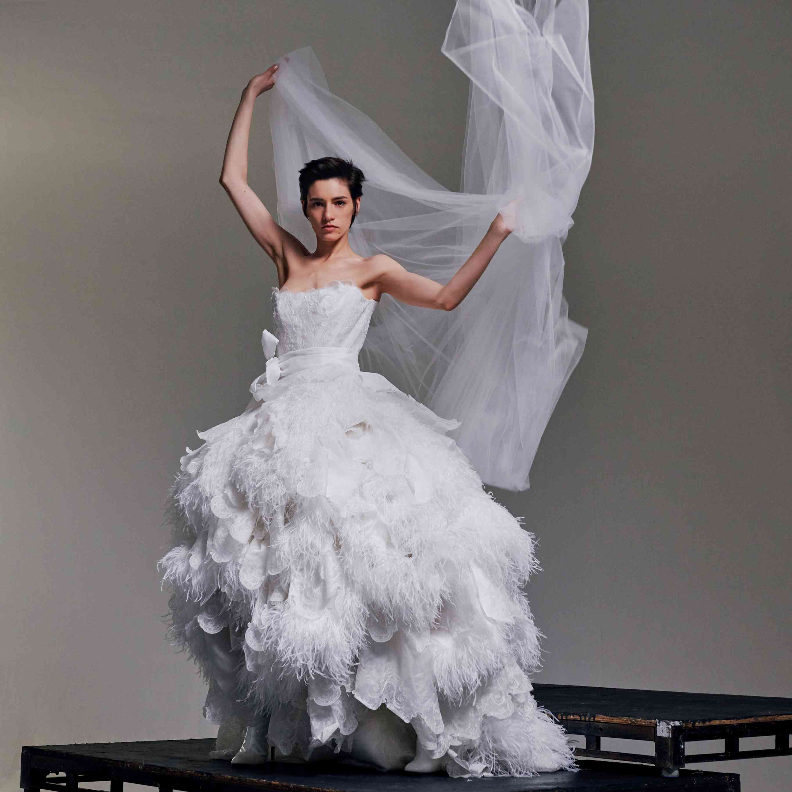 Model in feathered white wedding gown